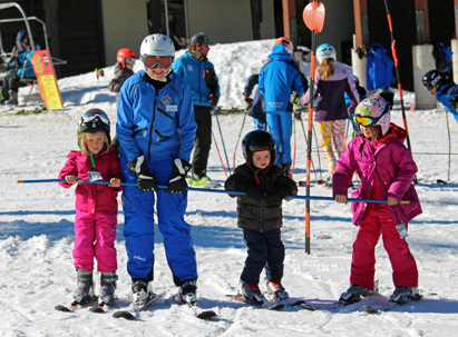 Ski Lessons - Small children taking a lesson with a sugar bowl instructor