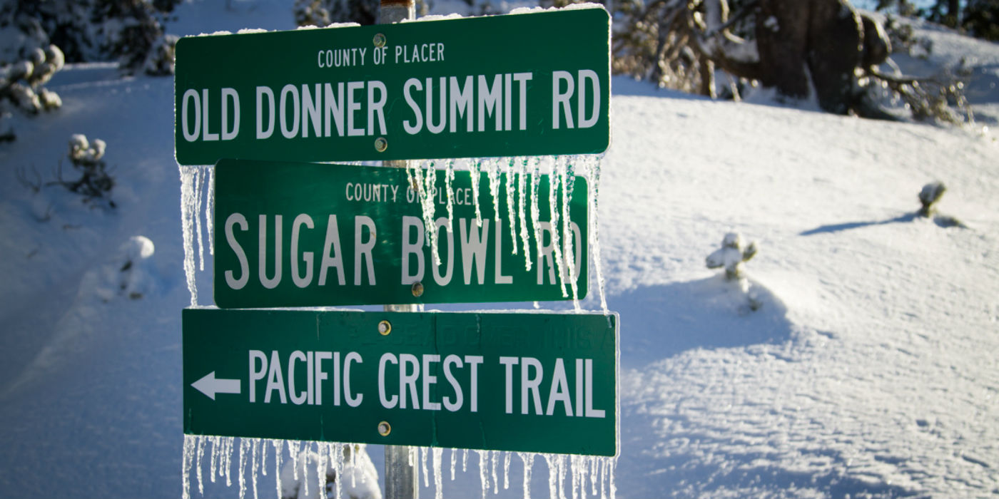 3 frozen green road signs with icicles hanging down. Old Donner Summit Road on top Sugar Bowl Road in the middle and a sign pointing to the Pacific Crest Trail on the bottom.