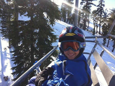 John Marco Henderson sitting on a chair lift at Sugar Bowl smiling and wearing his helmet with a blue jacket.