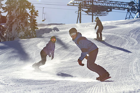 Two women snowboarders following a Sugar Bowl snowboard instructor on top of beautiful Mount Disney.