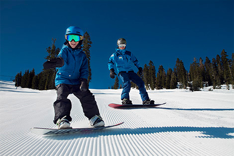Child snowboarder learning from his friendly Sugar Bowl snowboard instructor.