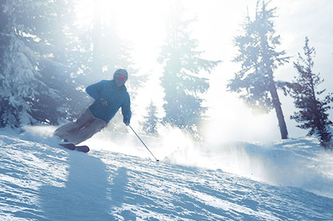 Skier enjoying discounted lift tickets on soft snow with the warm sun behind him.