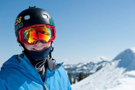 Skier smiling with a black helmet, red goggles and blue jacket.