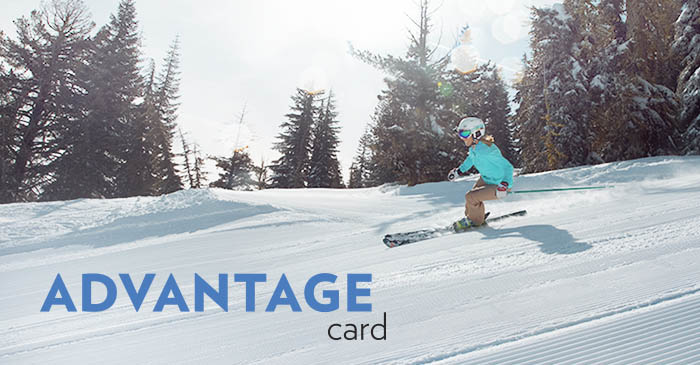 Skier wearing a teal jacket having fun skiing with discounted tickets on a nice groomed run. Advantage Card is overlaid in text.