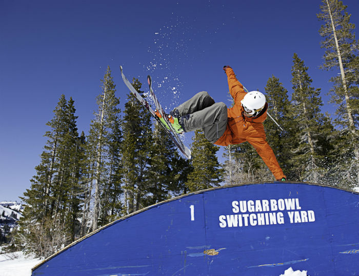 Sugar Bowl Terrain Park Rainbow Box with skier in orange jacket performing a hand plant.