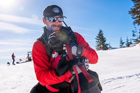 Ski Patrol Holding a black patrol working dog.