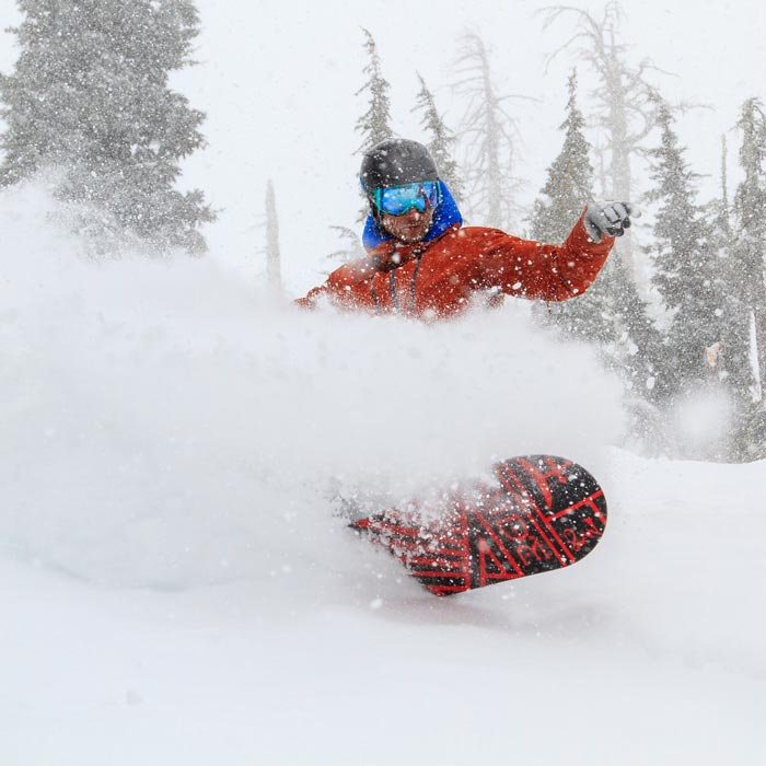 Man Snowboarding in beautiful Lake Tahoe down a run in deep powder at Sugar Bowl Ski Resort