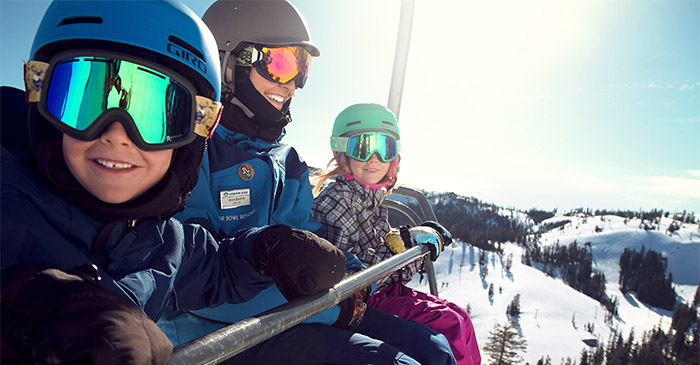 Two Kids with their instructor riding up the Disney Chairlift.