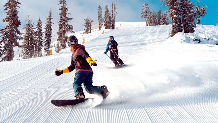 Female snowboarder riding a groomed run off Mount Lincoln at Sugar Bowl Ski Resort