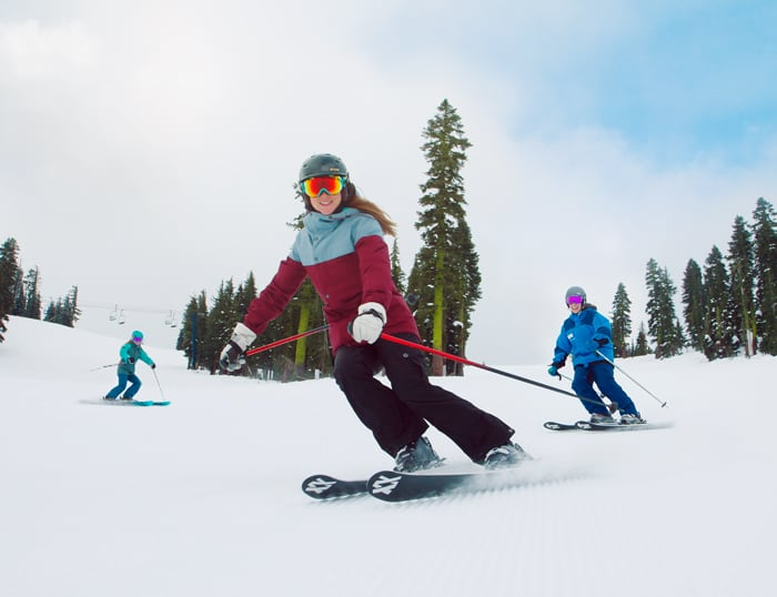 Group of women skiers improving their skills with a friendly instructor on a groomed run at Sugar Bowl Ski Resort