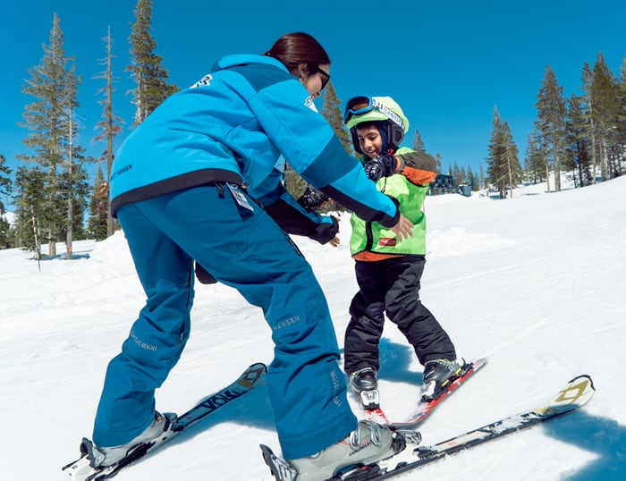 Friendly ski instructor teaching a young boy with a green helmet cover to ski.