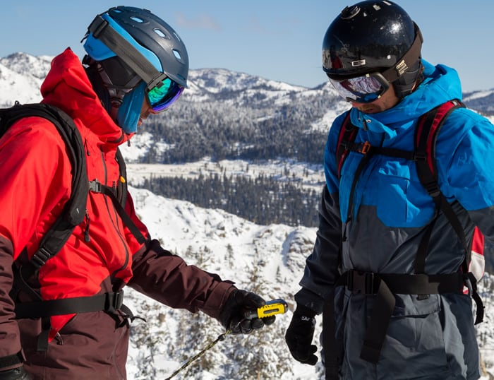 Two Backcountry Splitboarders checking their avalanche beacons before going in the backcountry.