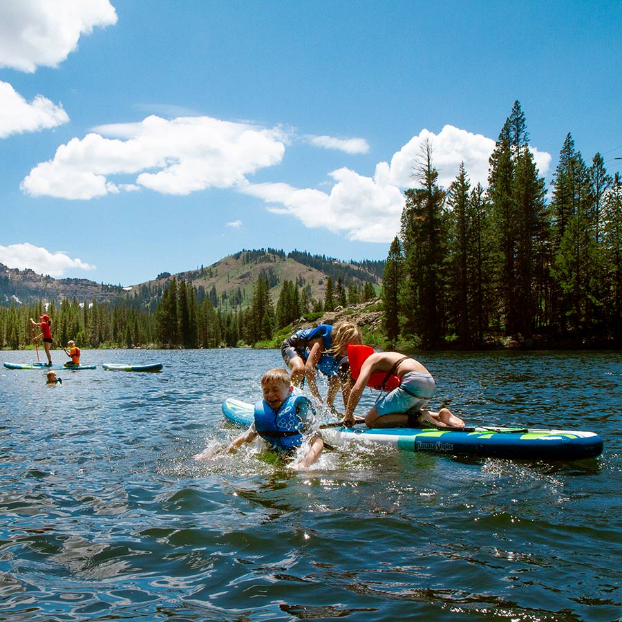 Campers paddle boarding and playing in Lake Mary at Sugar Bowl Summer Camp