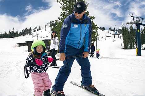 Friendly ski instructor teaching a young girl with a green helmet cover to ski.