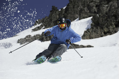 Skier in blue jacket turning on an off piste run in spring weather.