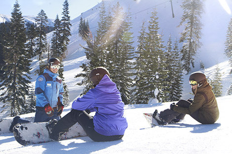 Group of new snowboarders listening to their Sugar Bowl instructor give a friendly lesson.