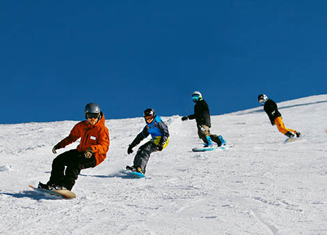 Snowboard team following their instructor and learning good snowboard techniques