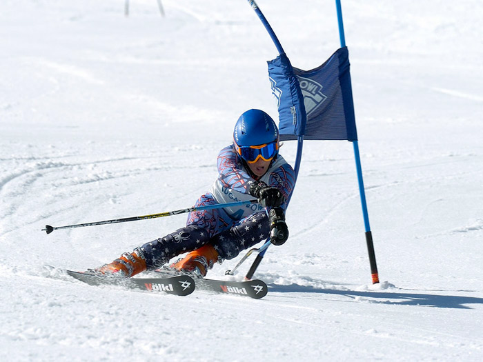 Ski racer making a hard left turn making contact with a Sugar Bowl race gate.