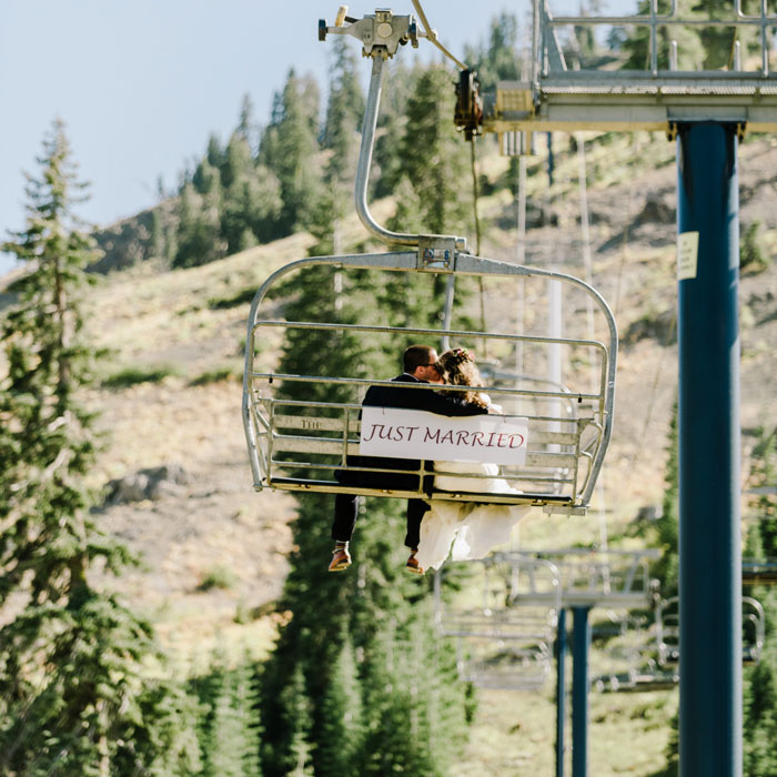 Bride and Groom riding a chairlift up Mt. Disney in the summer with a Just Married sign behind them