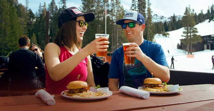 Couple enjoying burgers and beer on the deck of the Village Lodge at Sugar Bowl Ski Resort