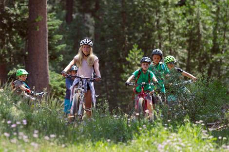 Kids Campers Mountain Bike through a flower meadow near Sugar Bowl Ski Resort.